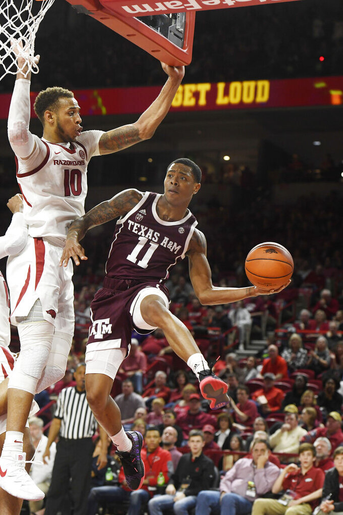 Texas A&M guard Wendell Mitchell (11) tries to get past Arkansas defender Daniel Gafford (10) during the second half of an NCAA college basketball game, Saturday, Feb. 23, 2019 in Fayetteville, Ark. (AP Photo/Michael Woods)
