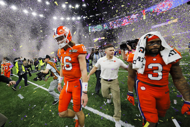 Clemson quarterback Trevor Lawrence, left, leaves the field after a NCAA College Football Playoff national championship game against LSU, Monday, Jan. 13, 2020, in New Orleans. LSU won 42-25.(AP Photo/Gerald Herbert)