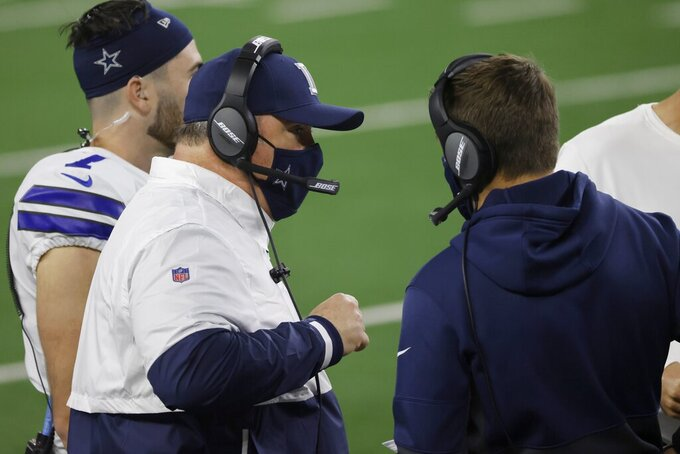 Dallas Cowboys head coach Mike McCarthy, left, talks with staff members in the second half of an NFL football game against the Arizona Cardinals in Arlington, Texas, Monday, Oct. 19, 2020. (AP Photo/Ron Jenkins)
