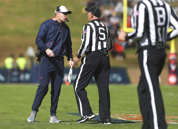 FILE - In this Oct. 27, 2018 file photo, Virginia head coach Bronco Mendenhall speaks to the officials between plays during the second half of an NCAA college football game against North Carolina in Charlottesville, Va. Now that the Virginia Cavaliers are ranked, bowl eligible and have announced that winning the ACC's Coastal Division is their goal, they want to maintain the focus that has led to a three-game winning streak. The Cavaliers next challenge comes Friday when they host Pittsburgh in an ACC matchup.(Zack Wajsgras  /The Daily Progress via AP, File)