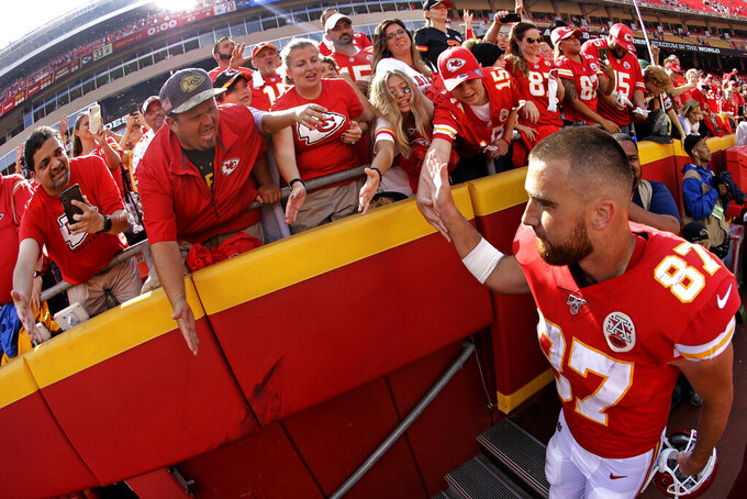 Kansas City Chiefs tight end Travis Kelce (87) greets fans as he walks off the field after an NFL football game against the Baltimore Ravens, Sunday, Sept. 22, 2019, in Kansas City, Mo. (AP Photo/Charlie Riedel)