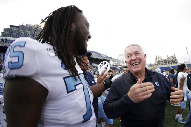 North Carolina head coach Mack Brown, right, reacts with offensive lineman Joshua Ezeudu, left, after Brown was doused with water during the second half of the Military Bowl NCAA college football game against Temple, Friday, Dec. 27, 2019, in Annapolis, Md. North Carolina won 55-13. (AP Photo/Julio Cortez)