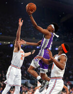 Sacramento Kings guard De'Aaron Fox (5) puts up a shot against New York Knicks forward Kevin Knox (20) and guard Damyean Dotson (21) during the first quarter of an NBA basketball game, Saturday, March 9, 2019, in New York. (AP Photo/Julie Jacobson)