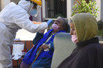 A healthcare worker takes samples to test elderly residents for the new coronavirus at the San Jose nursing home in Cochabamba, Bolivia, Friday, July 17, 2020. At least 60 residents at the senior care facility tested positive for the new coronavirus and 10 have died from related symptoms in the last two weeks, amid a rise in cases and fatalities in the Andean country. (AP Photo/Dico Solis)