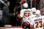 Calgary Flames assistant coach Paul Jerrard, left, fist-bumps left wing Ryan Lomberg (56) as the team leaves the ice after defeating the New Jersey Devils in an NHL hockey game, Thursday, Feb. 8, 2018, in Newark, N.J. The NHL has almost two dozen black players but just one black official in linesman Shandor Alphonso and one black coach in Flames assistant Paul Jerrard. (AP Photo/Julio Cortez)
