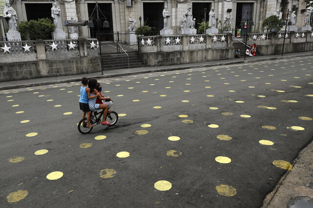 Children ride a bike past markers placed outside the Santo Nino Parish at Tondo district, Manila, Philippines on Friday, Jan. 15, 2021. The Manila city government said that the usual festivities are prohibited during the upcoming feast day of Santo Nino or Baby Jesus in Tondo and Pandacan to curb the spread of COVID-19 infections. Masses will be held at the church under strict health protocols this weekend. (AP Photo/Aaron Favila)