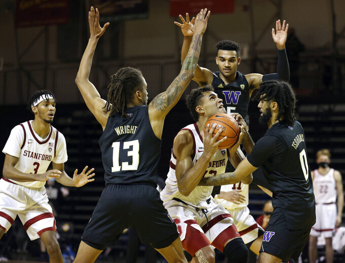 Washington forward Hameir Wright (13), left, guard Jamal Bey (5), center, and guard Marcus Tsohonis (0), right, defend against Stanford forward Oscar da Silva (13),center, who shoots during the second half of an NCAA college basketball game in Santa Cruz, Calif., Thursday, Jan. 7, 2021. (AP Photo/Josie Lepe)