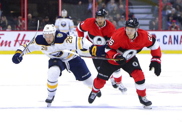 Ottawa Senators defenseman Erik Brannstrom (26) and Buffalo Sabres center Zemgus Girgensons (28) chase the puck during the first period of an NHL hockey game Monday, Dec. 23, 2019, in Ottawa, Ontario. (Sean Kilpatrick/The Canadian Press via AP)