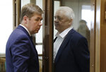 Norwegian national Frode Berg, who is accused of spying on Russia, speaks with his lawyer Ilya Novikov from inside a glass cage in a court room in Moscow, Russia, Tuesday, April 16, 2019. A Moscow court has found Berg guilty of espionage and sentenced him to 14 years in a high-security prison. (AP Photo/Pavel Golovkin)