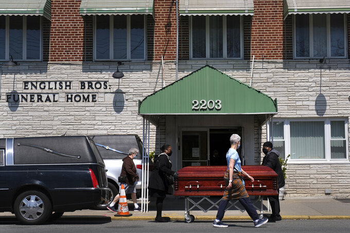 Pedestrians walk past the English Bros Funeral Home as a casket is unloaded in the Brooklyn borough of New York, Sunday, April 19, 2020. New York's daily toll of coronavirus deaths has hit its lowest point in more than two weeks, but officials still warn that New York City and the rest of the state aren't ready to ease up on shutdowns of schools, businesses and gatherings. Mayor Bill de Blasio warned Sunday that with the arrival of spring weather, the city will step up enforcement of social distancing rules. (AP Photo/Seth Wenig)