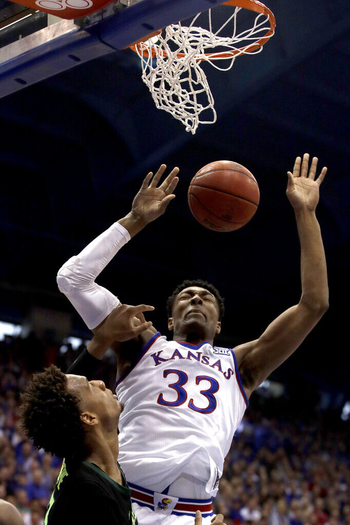 Kansas' David McCormack (33) gets past Baylor's Freddie Gillespie to dunk the ball during the first half of an NCAA college basketball game Saturday, March 9, 2019, in Lawrence, Kan. (AP Photo/Charlie Riedel)