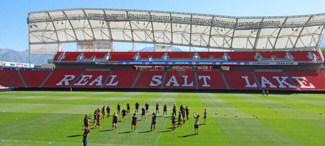 FILE - In this Sept. 12, 2014 file photo, members of the U.S. Women's National team warm up during practice at Rio Tinto Stadium in Sandy, Utah. Pro soccer returns to the U.S. next month when the National Women's Soccer League starts a 25-game tournament in a pair of stadiums in Utah that will be kept clear of fans to protect players from the coronavirus. Players from the nine teams will train and live at two Salt Lake City-area hotels, the league announced Wednesday, May 27, 2020. (AP Photo/Rick Bowmer, File)