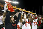 FILE - In this Nov. 25, 2017, file photo, Wisconsin players hold up Paul Bunyan's Axe up after winning 31-0 against Minnesota in an NCAA college football game, in Minneapolis. More than Paul Bunyan's Axe is on the line in college football's most-played rivalry. The winner of Saturday's game between No. 9 Minnesota and No. 13 Wisconsin wins a division title, and plays No. 2 Ohio State in the Big Ten title game. (AP Photo/Stacy Bengs, File)