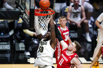 Purdue forward Trevion Williams (50) is fouled on a dunk in front of Wisconsin forward Micah Potter (11) during the second half of an NCAA college basketball game in West Lafayette, Ind., Tuesday, March 2, 2021. (AP Photo/Michael Conroy)
