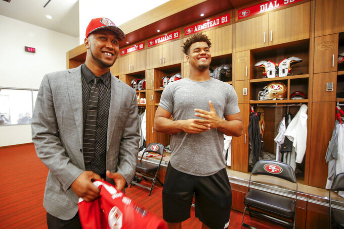 FILE - In this Friday, April 29, 2016, file photo, San Francisco 49ers NFL first round draft pick DeForest Buckner, left, a defensive lineman from Oregon, meets with former Oregon teammate Arik Armstead, right, during an NFL football news conference in Santa Clara, Calif. Armstead and Buckner have been teammates on the defensive line for seven of the past eight seasons whether in college at Oregon or in the NFL with the San Francisco 49ers. The 49ers signed Armstead to a five-year contract worth up to $85 million on Monday, March 16, 2020, and then immediately agreed to a deal to send Buckner to Indianapolis. (AP Photo/Tony Avelar, File)