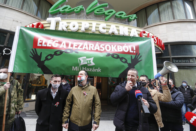"""Hungarians hold a banner that reads """"Stop the Restrictions"""" during a protest in Budapest, Hungary, Monday, March 15, 2021. Hungarians gathered on the country's national day to protest against the current lockdown measures after new restrictive measures were introduced by the Hungarian government last week aiming to slow a record-breaking wave of COVID-19 hospitalizations and deaths. (AP Photo/Laszlo Balogh)"""