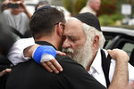 FILE - In this April 28, 2019, file, photo, Rabbi Yisroel Goldstein, right, is hugged as he leaves a news conference at the Chabad of Poway synagogue in Poway, Calif. A man opened fire inside the synagogue near San Diego as worshippers celebrated the last day of a major Jewish holiday. Israeli researchers reported Wednesday, May 1, 2019, that violent attacks against Jews spiked significantly last year, with the largest reported number of Jews killed in anti-Semitic acts in decades, leading to an