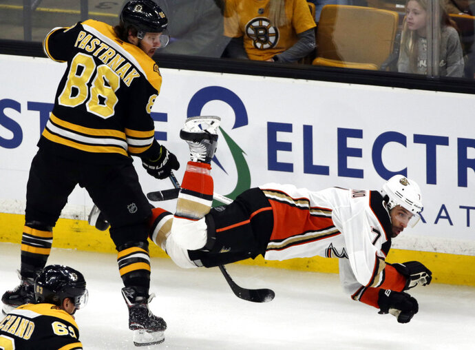 Boston Bruins right wing David Pastrnak (88) dumps Anaheim Ducks left wing Andrew Cogliano (7) to the ice in the first period of an NHL hockey game, Thursday, Dec. 20, 2018, in Boston. (AP Photo/Elise Amendola)
