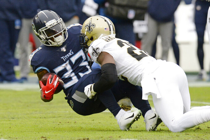 Tennessee Titans running back Dion Lewis (33) is stopped by New Orleans Saints defensive back Chauncey Gardner-Johnson (22) in the first half of an NFL football game Sunday, Dec. 22, 2019, in Nashville, Tenn. (AP Photo/Mark Zaleski)
