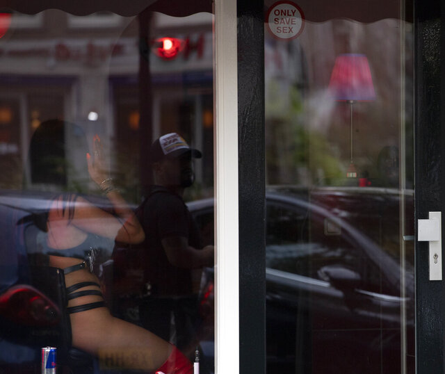 A sex worker shields her face from the photographer as a passing man is reflected in the window after a further ease of corona virus restrictions in Amsterdam, Netherlands, Wednesday, July 1, 2020. It wasn't quite business as usual as the capital's Red Light District emerged from coronavirus lockdown, but it was as close as it has been since the pandemic slammed the brakes on the world's oldest profession. (AP Photo/Peter Dejong)