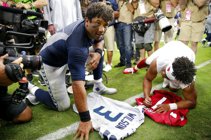 Seattle Seahawks quarterback Russell Wilson, left, and Arizona Cardinals quarterback Kyler Murray, left, exchange jerseys after an NFL football game, Sunday, Sept. 29, 2019, in Glendale, Ariz. (AP Photo/Rick Scuteri)