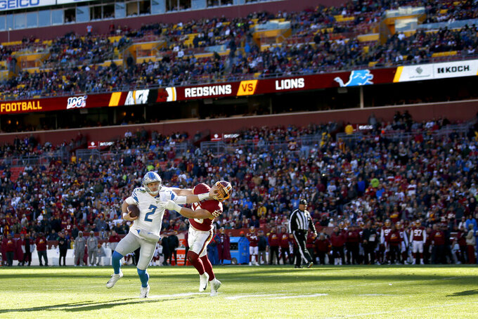 Detroit Lions quarterback Jeff Driskel (2) applies a stiff arm on Washington Redskins linebacker Cole Holcomb (55) during the first half of an NFL football game, Sunday, Nov. 24, 2019, in Landover, Md. (AP Photo/Alex Brandon)
