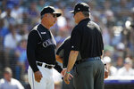 Colorado Rockies manager Bud Black, left, confers with third base umpire Gary Cederstrom after Chicago Cubs relief pitcher Brad Brach hit Colorado's Tony Wolters with a pitch during the ninth inning of a baseball game Wednesday, June 12, 2019, in Denver. The Cubs won 10-1. (AP Photo/David Zalubowski)