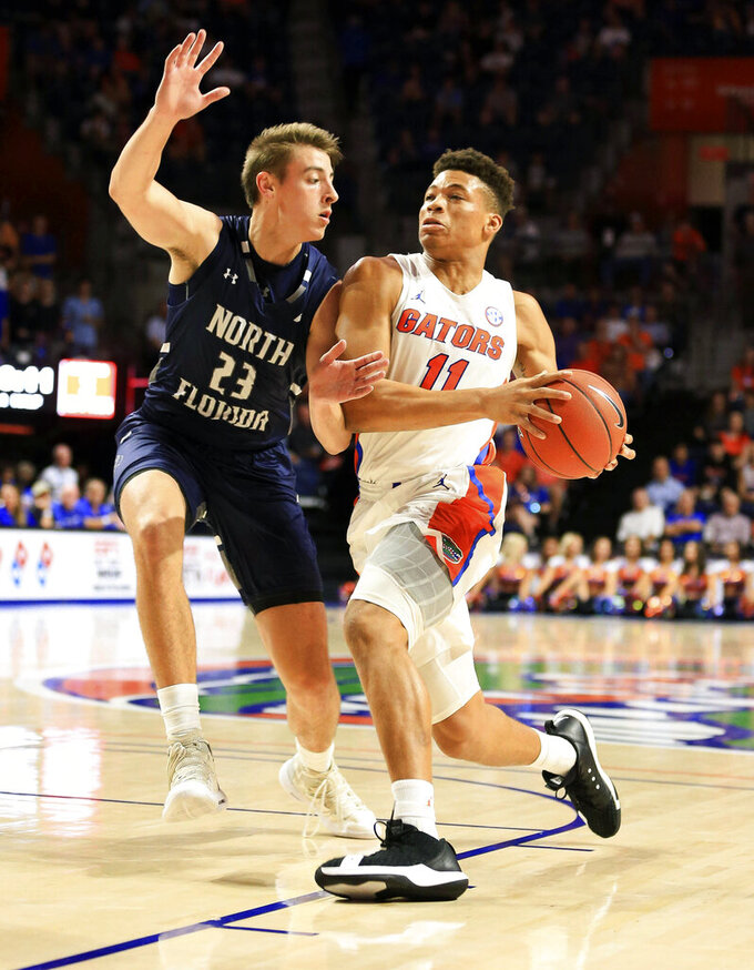 Florida forward Keyontae Johnson (11) drives past North Florida forward Carter Hendricksen (23) during the first half of an NCAA college basketball game Tuesday, Nov. 5, 2019, in Gainesville, Fla. (AP Photo/Matt Stamey)