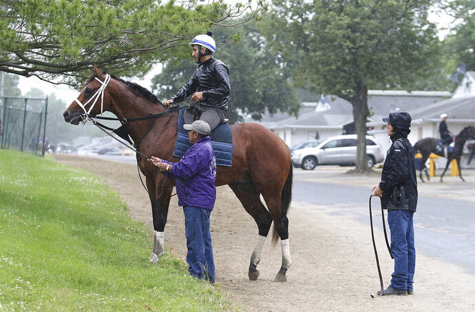 Maximum Security, ridden by exercise rider Edelberto Rivas up, pauses after a morning gallop as assistant trainer Jose Hernandez and Jason Servis, right, to look on at Monmouth Park, Thursday, June 13, 2019, in Oceanport, N.J. Maximum Security will make his next start in Sunday's $150,000 Pegasus Stakes horse race at the track. (Bill Denver/EQUI-PHOTO via AP)