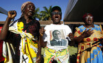 Mourners sing as they honour the late former President Robert Mugabe, on the lawn of his homestead in Kutama village, 85 km (52 miles) southeast of Harare, Zimbabwe, Monday, Sept. 9, 2019. Mugabe, who enjoyed strong backing from Zimbabwe's people after taking over in 1980, but whose support waned following decades of repression, economic mismanagement and allegations of election-rigging, is expected to be buried on Sunday, state media reported. (AP Photo/Themba Hadebe)