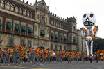 Performers in monarch butterfly costumes wave to the crowd as they walk in a Day of the Dead parade in Mexico City, Sunday, Oct. 27, 2019. The parade on Sunday marks the fourth consecutive year that the city has borrowed props from the opening scene of the James Bond film,