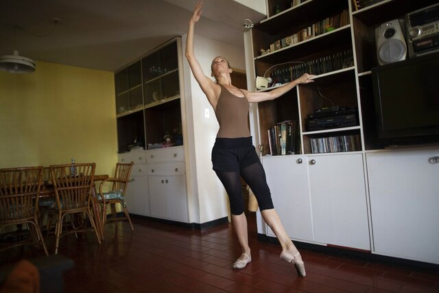 Carolina Wolf, who dances with Venezuela's national ballet, trains in her living room where she adapted her bookshelf to take the place of her ballet bar, during a lockdown to curb the spread of COVID-19 in Caracas, Venezuela, Tuesday, Aug. 11, 2020. The 42-year-old ballerina said her living room is four times smaller than the studio where she practiced daily at the famed Teresa Carreño Theater, and she doesn't dare do jumps in fear of injuring herself on the hard floor. (AP Photo/Ariana Cubillos)