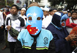 A Muslim youth wears a pro-independence mask with an Eastern Turkistan flag during a rally outside the Chinese Embassy in Jakarta, Indonesia, Friday, Dec. 27, 2019. Over a thousand Muslims staged the rally calling to an end to alleged oppression against Muslim Uighur ethnic minority in China's region of Xinjiang. (AP Photo/Dita Alangkara)