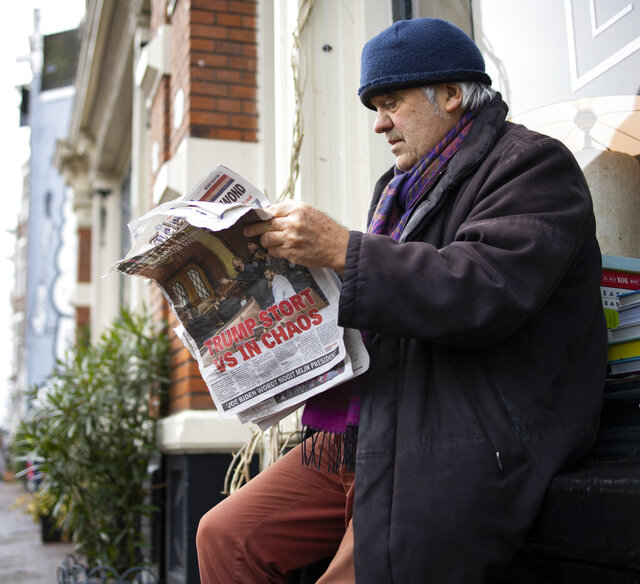 A man reads a newspaper with a headline reading