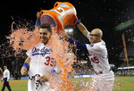 Los Angeles Dodgers' Cody Bellinger (35), is doused by teammate Matt Beaty after drawing a bases-loaded walk to end a baseball game against the Arizona Diamondbacks on Tuesday, July 2, 2019, in Los Angeles. Los Angeles won 5-4. (AP Photo/Marcio Jose Sanchez)