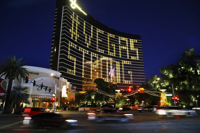 """Hotel room lights spell out """"Vegas Strong"""" at the Wynn hotel-casino along the Las Vegas Strip as casinos and other business are shuttered due to the coronavirus outbreak Wednesday, April 1, 2020, in Las Vegas. (AP Photo/John Locher)"""