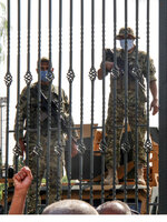 Tunisian soldiers guard the main entrance of the parliament as demonstrators gather outside the the gate in Tunis, Tunisia, Monday, July 26, 2021. Troops surrounded Tunisia's parliament and blocked its speaker from entering Monday after the president suspended the legislature and fired the prime minister following nationwide protests over the country's economic troubles and the government's handling of the coronavirus crisis. (AP Photo/Hedi Azouz)