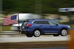 FILE - In this May 28, 2021 file photo, a motorist from Massachusetts flies an American flag ahead of the Memorial Day holiday while traveling on the Maine Turnpike in Kennebunk, Maine. The number of highway deaths in 2020 was the greatest in more than a decade even though cars and trucks drove fewer miles during the pandemic, and motorists are continuing to speed, tailgate and zigzag through traffic. (AP Photo/Robert F. Bukaty)