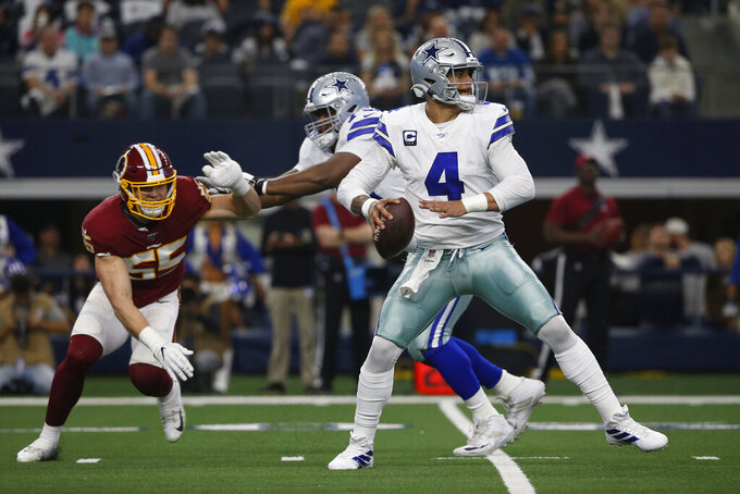 Dallas Cowboys quarterback Dak Prescott (4) is pressured by Washington Redskins linebacker Cole Holcomb (55) during the first half of an NFL football game in Arlington, Texas, Sunday, Dec. 15, 2019. (AP Photo/Ron Jenkins)