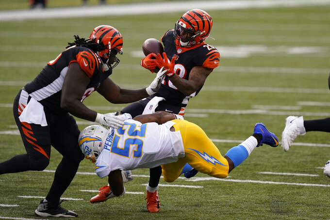 Cincinnati Bengals running back Joe Mixon (28) fumbles as he is hit by Los Angeles Chargers' Denzel Perryman (52) during the second half of an NFL football game, Sunday, Sept. 13, 2020, in Cincinnati. (AP Photo/Bryan Woolston)