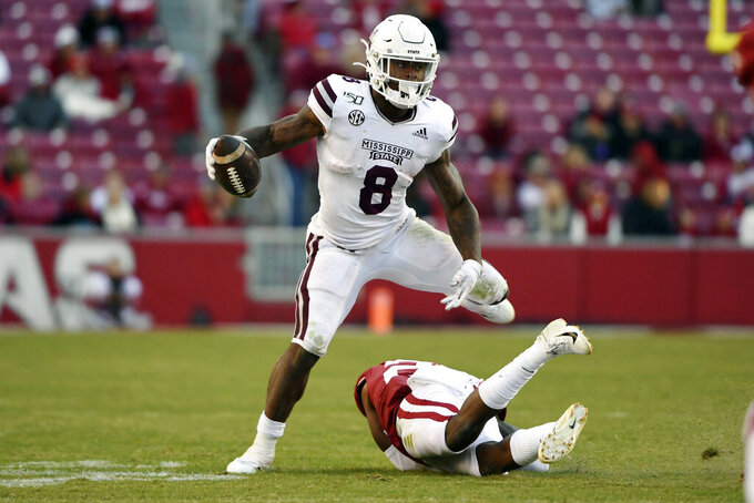 Mississippi State running back Kylin Hill (8) shakes Arkansas defender Andrew Parker as he runs for a gain during the second half of an NCAA college football game, Saturday, Nov. 2, 2019 in Fayetteville, Ark. (AP Photo/Michael Woods)