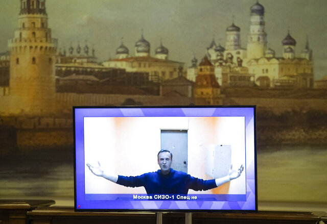 Russian opposition leader Alexei Navalny appears on a TV screen during a live session with the court during a hearing of his appeal in a court in Moscow, Russia, Thursday, Jan. 28, 2021, with an image of the Moscow Kremlin in the background. Navalny was jailed soon after arriving to Moscow after authorities accused him of violating of the terms of his 2014 fraud conviction. A court on Thursday is to hear an appeal on the ruling to remand him into custody. Next week, another court will decide whether to send him to prison for several years for the alleged violations. (AP Photo/Pavel Golovkin)
