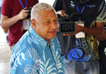 FILE - In this Sept. 17, 2014 file photo, Fiji's military ruler Voreqe Bainimarama arrives at a polling station to cast his vote in a national election in Suva, Fiji. From 2009 until 2011, the regime led by Bainimarama installed censors at news outlets, including the Fiji Times, to control what was being printed and broadcast. An opinion writer and three newspaper executives in Fiji are awaiting a judge's verdict Friday, May 18, 2018 on sedition charges in a case that has major implications for press freedom in the South Pacific nation. (AP Photo/Pita Ligaiula, File)
