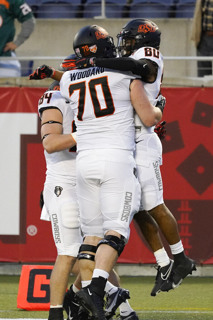 Oklahoma State wide receiver Brennan Presley (80) celebrates his touchdown reception against Miami with offensive lineman Hunter Woodard (70) and tight end Dayton Metcalf (84) during the first half of the Cheez-it Bowl NCAA college football game, Tuesday, Dec. 29, 2020, in Orlando, Fla. (AP Photo/John Raoux)