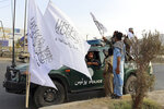 Taliban fighters buy Taliban flags in Kabul, Afghanistan, Monday, Aug. 30, 2021. Many Afghans are anxious about the Taliban rule and are figuring out ways to get out of Afghanistan. But it's the financial desperation that seems to hang heavy over the city. (AP Photo/Khwaja Tawfiq Sediqi)
