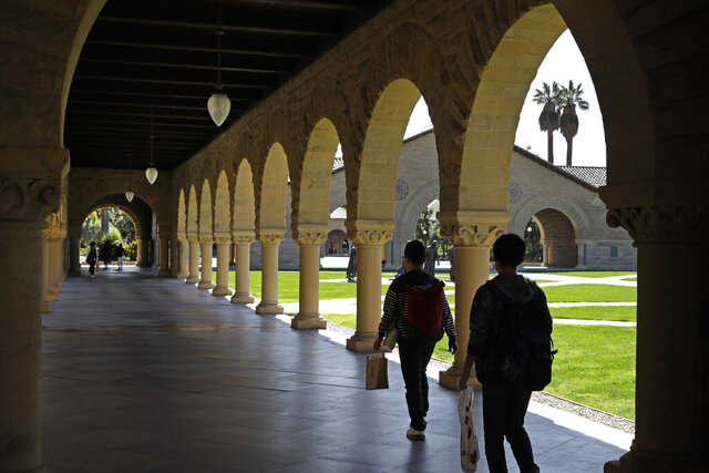 FILE - In this March 14, 2019, file photo people walk on the Stanford University campus in Santa Clara, Calif. Seven percent of employers offer student loan repayment assistance as a benefit. For most companies, this benefit means making a direct payment to eligible employees' loan. (AP Photo/Ben Margot, File)