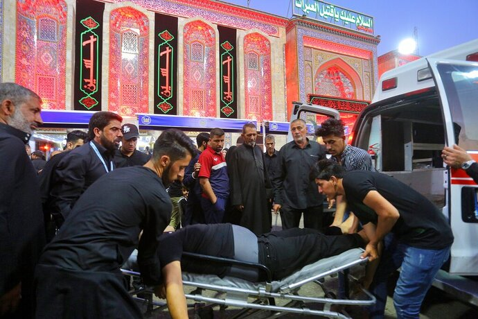 People evacuate an injured man after a walkway collapsed and set off a stampede as thousands of Shiite Muslims marked one of the most solemn holy days of the year in the holy city of Karbala, Iraq, Tuesday, Sept. 10, 2019. Officials say at least 31 people have died and around 100 others were injured in the chaos Tuesday, which occurred toward the end of the Ashoura procession, causing panic and a stampede, according to two officials. (AP Photo/Anmar Khalil)