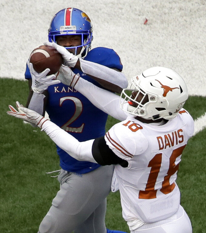 Kansas wide receiver Daylon Charlot (2) catches a touchdown pass while covered by Texas defensive back Davante Davis (18) during the second half of an NCAA college football game in Lawrence, Kan., Friday, Nov. 23, 2018. Texas defeated Kansas 24-17. (AP Photo/Orlin Wagner)