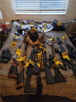 This photo provided by U.S. Attorney for the Middle District of Tennessee shows an evidence photo showing assault rifles that were found during a search of Eric Munchel's home.  In a court filing ahead of a Friday, Jan. 22, 2021 detention hearing, prosecutors describe a search of  Munchel's home that turned up assault rifles, a sniper rifle with a tripod, shotguns, pistols, hundreds of rounds of ammunition, and a drum-style magazine. Prosecutors also said they have reason to believe Munchel may have had weapons with him in Washington D.C. that he stashed outside the Capitol before entering.  (U.S. Attorney for the Middle District of Tennessee  via AP)