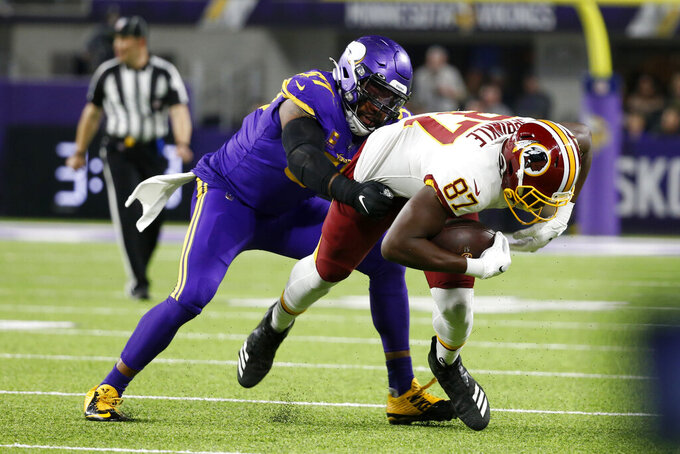Washington Redskins tight end Jeremy Sprinkle (87) is tackled by Minnesota Vikings defensive end Everson Griffen, left, after catching a pass during the first half of an NFL football game, Thursday, Oct. 24, 2019, in Minneapolis. (AP Photo/Bruce Kluckhohn)